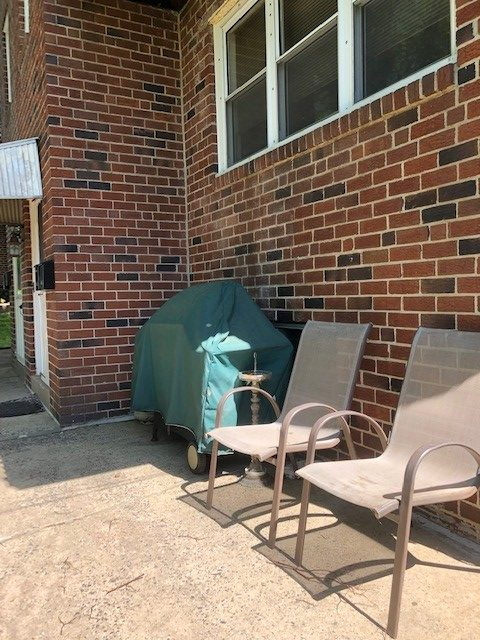 245 Abbey Terrace exterior chairs and grill against brick wall