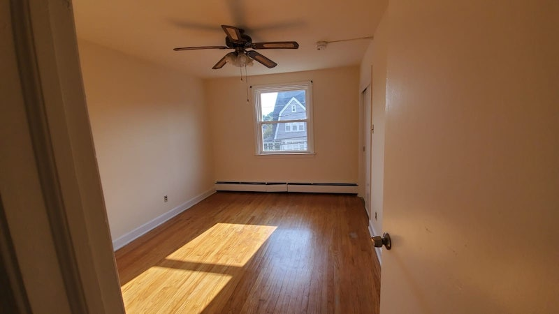 31 E. Lacrosse interior bedroom with hardwood floors and ceiling fan